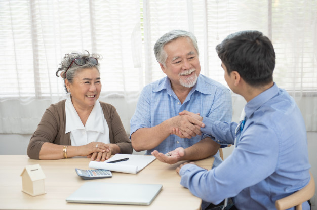 smiling-satisfied-senior-couple-making-sale-purchase-deal-concluding-contract-hand-get-house-key-from-real-estate-agent-happy-older-family-broker-shake-hands-agreei